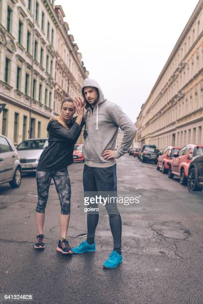 young sports couple standing in city streets