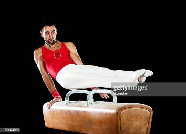 Young sportsman exercising on pommel horse.