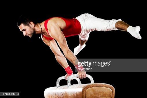 Young sportsman exercising on pommel horse.
