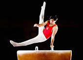 Young muscular man doing gymnastic exercises on pommel horse.