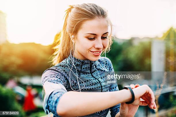 Young sportswoman checking her smart watch