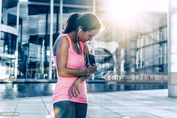 young sportswoman checking smartphone after jogging