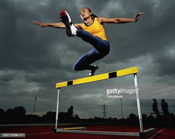 Young sportswoman hurdling, low angle view