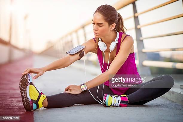 Giovane donna che ama gli sport all'esercizio di stretching dopo sessione cardio