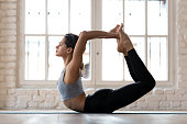 Young sporty attractive woman practicing yoga, doing Dhanurasana exercise, Bow pose, working out, wearing sportswear, pants and top, indoor full length, yoga studio