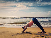 Vintage retro effect filtered hipster style image of Yoga outdoors - young sporty fit woman doing Ashtanga Vinyasa yoga asana Adho mukha svanasana - downward facing dog - at tropical beach on sunset.