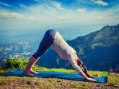 Yoga outdoors - young sporty fit woman doing Ashtanga Vinyasa Yoga asana Adho mukha svanasana - downward facing dog - in Surya Namaskar Sun Salutation outdoors in Himalayas in the morning. Vintage ret