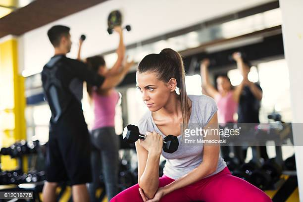 Young sporty woman doing dumbbell exercise at the gym.