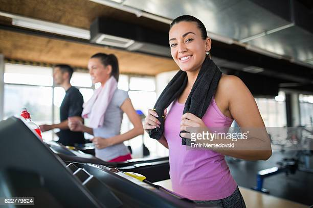 Young sporty woman exercising on treadmill at the gym