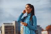 Young sporty woman listens to music via a smartphone and earbuds