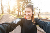 Young Sporty Woman Taking a Selfie at Park. She is Looking at Camera, that is the POV, Point of View, of the photo. She has a Smart Phone Holder on her Arm and Listen Music with Earphones.