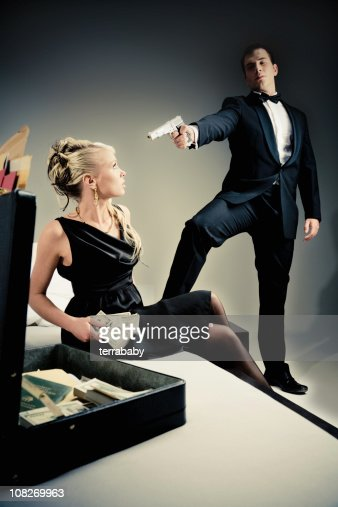 Young Spy Man Holding Gun to Woman Looking Through Suitcase : Stock Photo