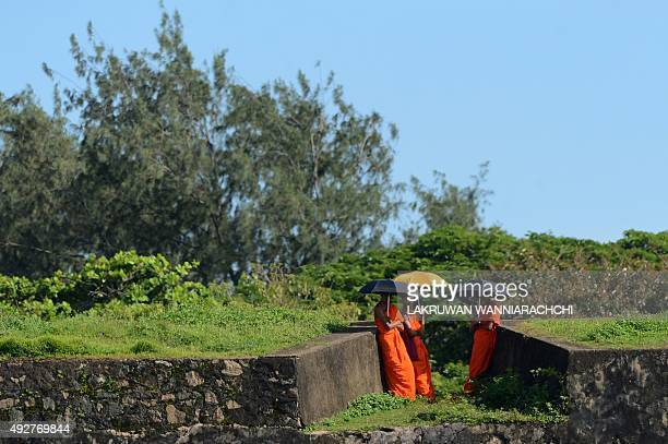 Young Sri Lankan Buddhist monks watch the second day of the opening Test match between Sri Lanka and the West Indies from the 16thcentury Dutch fort...
