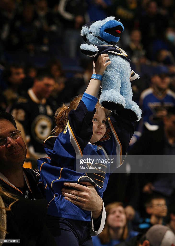 A young St. Louis Blues fan cheers on her team in an NHL game between the St. Louis Blues and the Minnesota Wild on January 27, 2013 at Scottrade Center in St. Louis, Missouri.