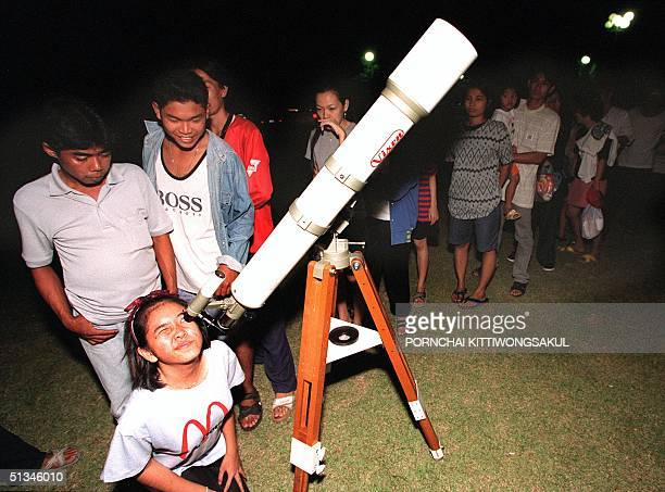A young stargazer looks through a telescope as others queue for a view of the Leonids meteor shower in central province of Ayutthaya early Wednesday...