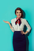 Beautiful dark haired young business woman dressed in a dark blue suit with a red, blue scarf standing and showing to her right side with hand, isolated on blue background. Stewardess