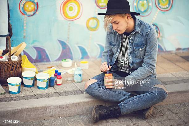 Young street artist preparing paint for painting a wall.