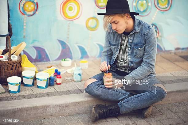 Jovem Artista de Rua preparação de Tinta para pintura de uma parede.