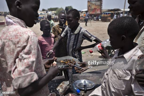 Young street vendors roast meat in the lively Kalibalek market in Bentiu town on March 22 2014 Bentiu town is cautiously going back to normality...