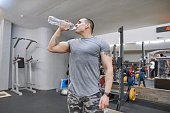 Young strong muscular man in gym drinking water from bottle.