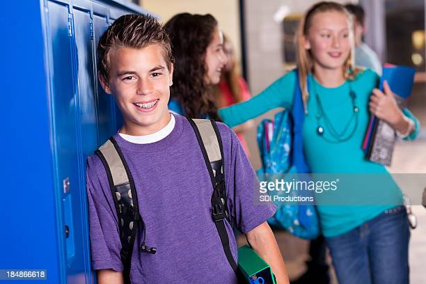 Young student at school lockers with friends