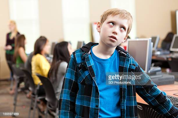 Young student bored in the school computer lab