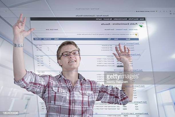 Young student celebrating examination results displayed on screen