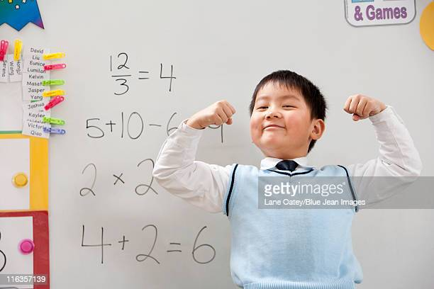 A young student flexing his muscles in front of a whiteboard