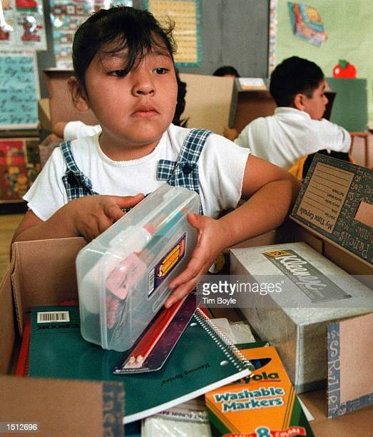 A young student in Loyda Camacho's secondgrade class digs through her 'GradeREADY' school supplies box August 22 2000 at Chicago's Stewart Elementary...