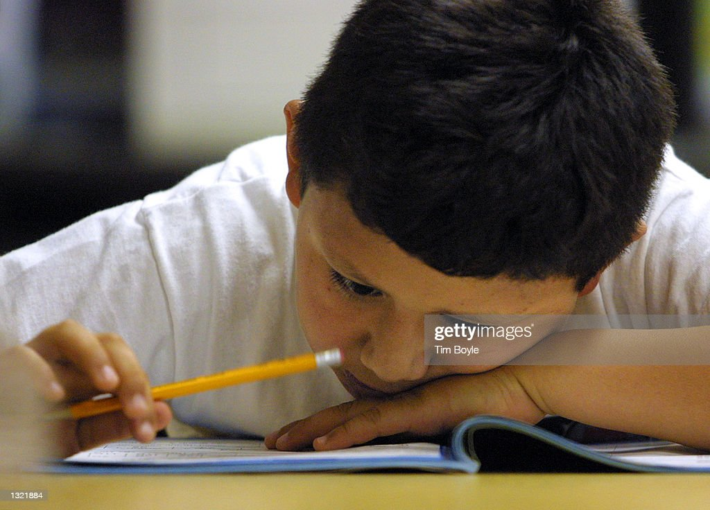 A young student in Ms McFaul''s second grade Early Intervention Bilingual class looks closely at a math exam during a summer school June 3 2001 at...