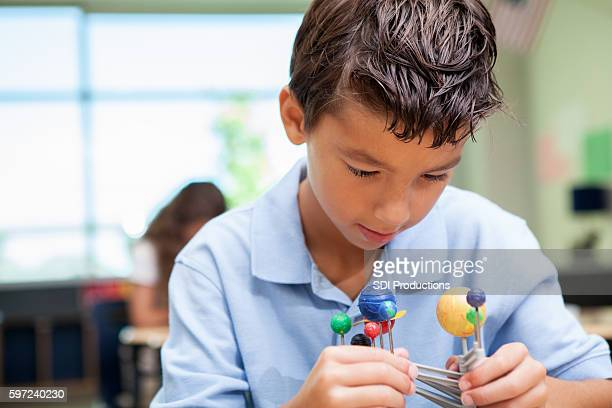 Young student in science class studying solar system model