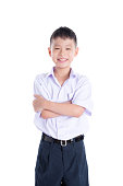 Young asian student boy in uniform smiling over white background