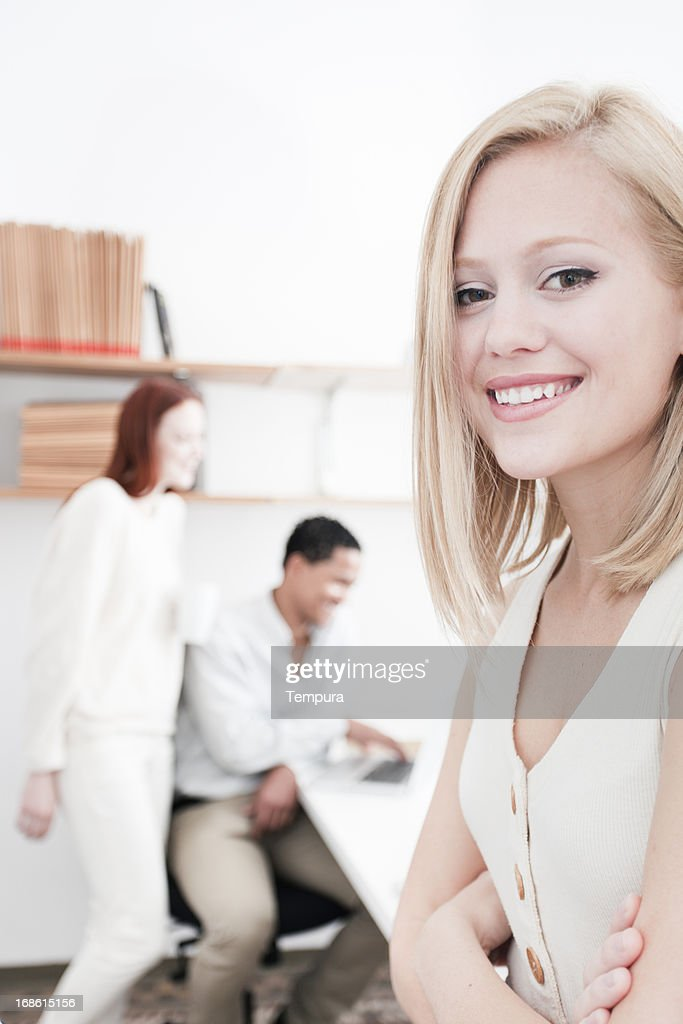 Young student looking at camera, more students in background : Stock Photo