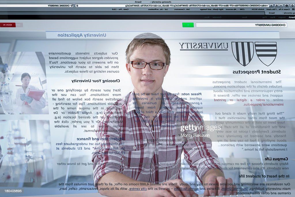 Young student looking at university prospectus on screen