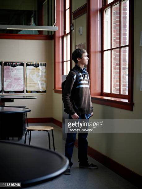 Young student looking out windows of classroom