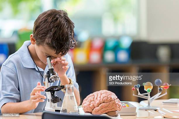 Young student looks through magnifying glass