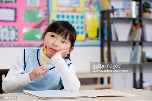 Young student raising her hand in classroom