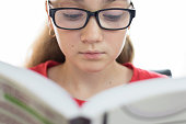 Portrait of a beautiful and young female student reading a book in closeup on a white background