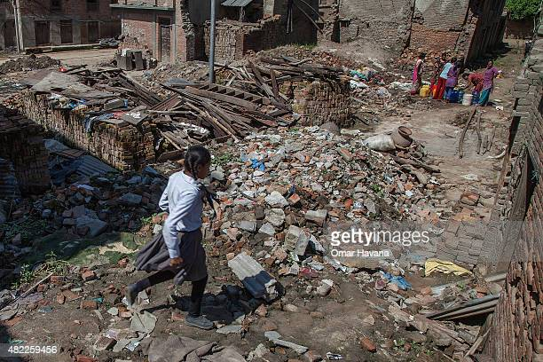 A young student runs in a street covered by debris from collapsed buildings on July 29 2015 in Bhaktapur Nepal Three months after the earthquake that...