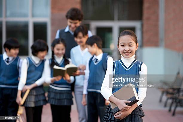 Young student standing confidently in the foreground