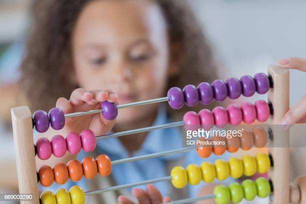 Young student uses abacus at school