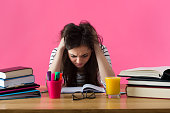 Frustrated female student. Young student with desperate expression sitting at her desk.