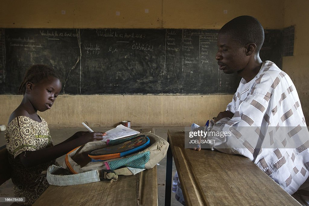 A young student writes during a lesson with teacher Isaika Maiga (R) at Thionville Chateau school in Gao, Mali on April 12, 2013. AFP PHOTO / JOEL SAGET