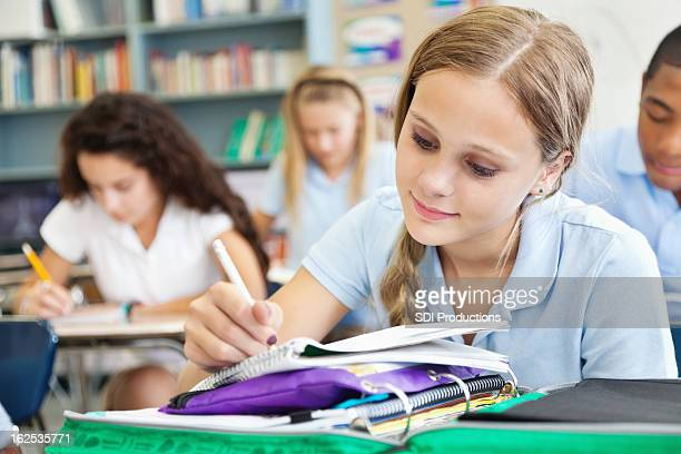 Young student writing in class full of students