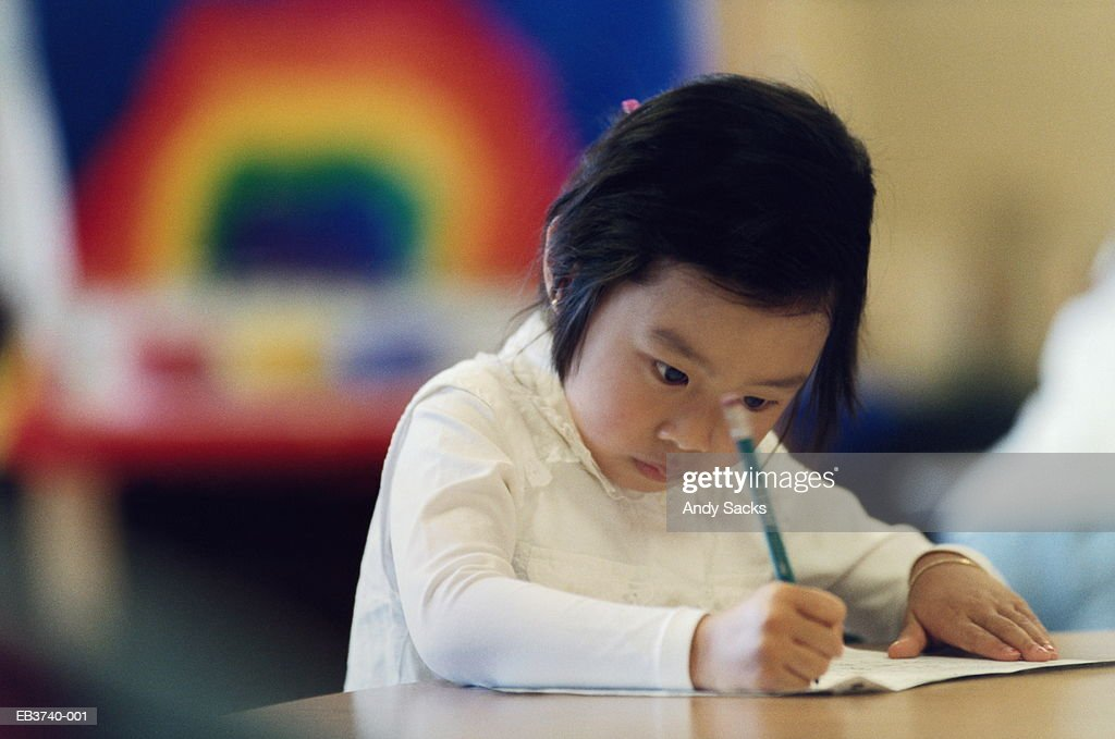 Young student (4-6) writing in classroom : Stock Photo