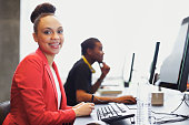 Happy young african american woman sitting in front of computer smiling at camera. Young students sitting at table using computers at school.
