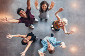 Top view of young students standing together looking up at camera with their hands raised in celebration.