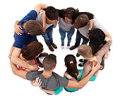 High angle view of young university students forming huddle against white background