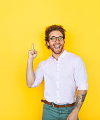 Handsome smart man in eyeglasses and white shirt pointing up on yellow looking excited.