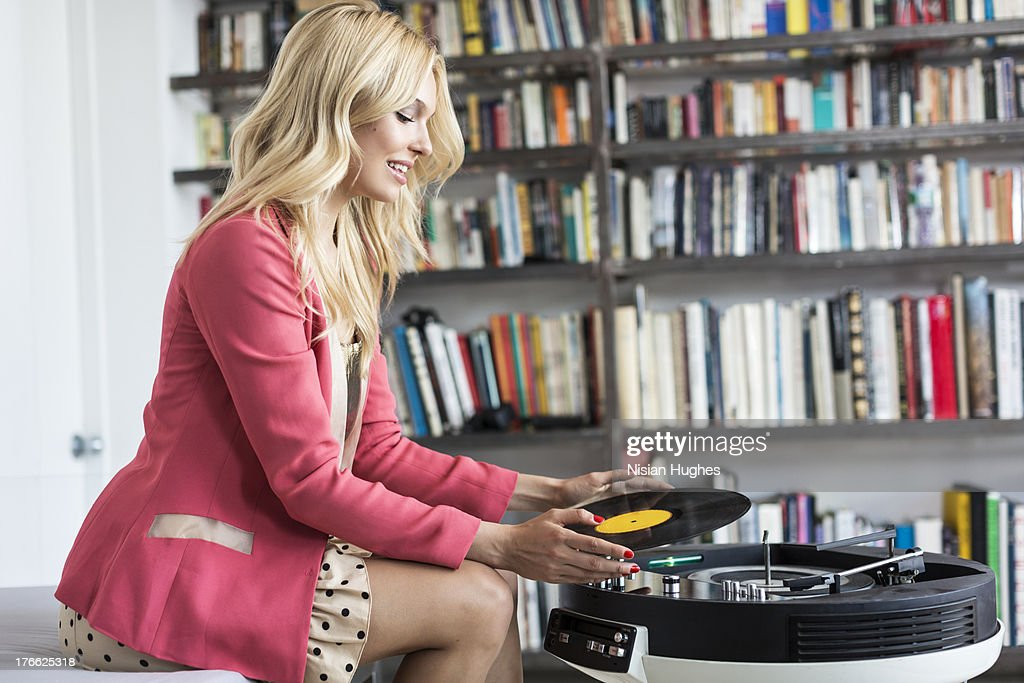 Young stylish woman putting on a record